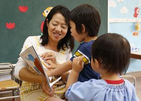 絵本を読む園児と先生