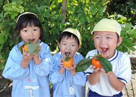 柿を手に持つ園児たち
